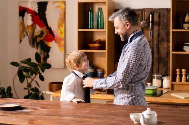 Pai amarrar gravata para filho pequeno Foto Premium