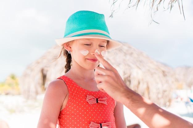 Pai, aplicar protetor solar no nariz da filha. Foto Premium