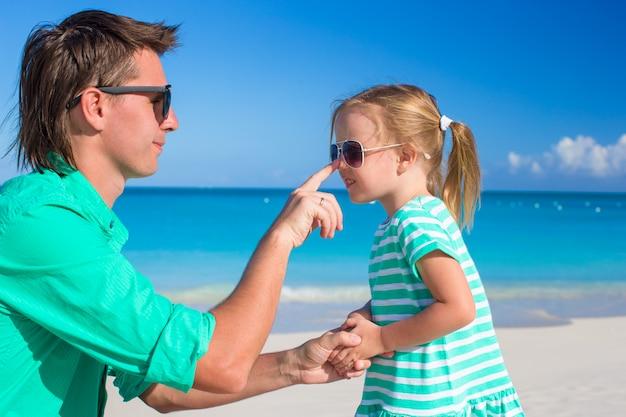 Pai aplique creme protetor solar no nariz de criança pequena Foto Premium