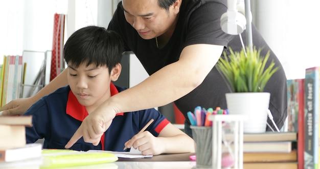 Pai asiático e filho que fazem trabalhos de casa em casa. Foto Premium
