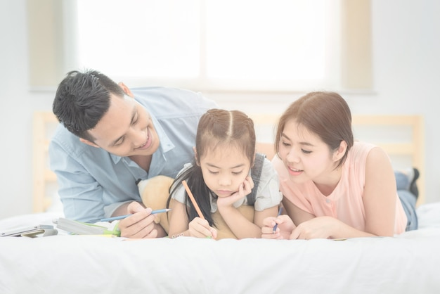 Pai asiático e mãe que ensinam sua criança da filha a estudar em casa. Foto Premium