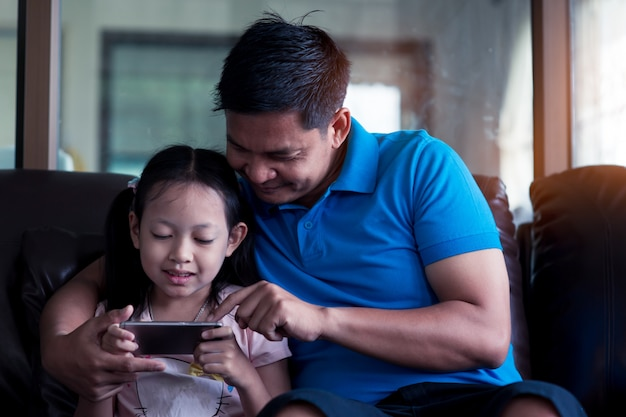 Pai asiático e sua filha usando smartphone em casa Foto Premium