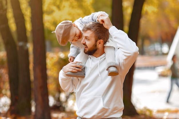 Pai bonito em um suéter cinza, brincando com a filha pequena em um parque de outono Foto gratuita