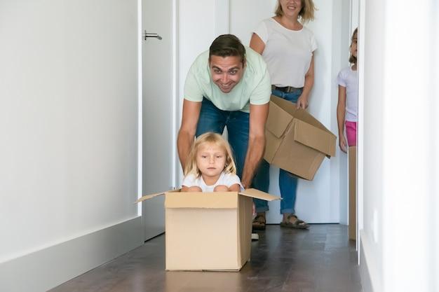 Pai brincalhão empurrando caixa de papelão com uma linda garota dentro Foto gratuita