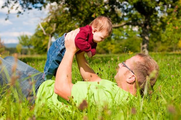 Pai brincando com bebê no prado Foto Premium