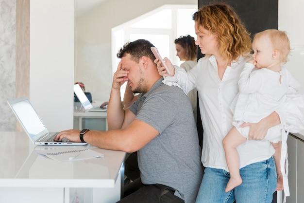 Pai cansado trabalhando no laptop Foto gratuita