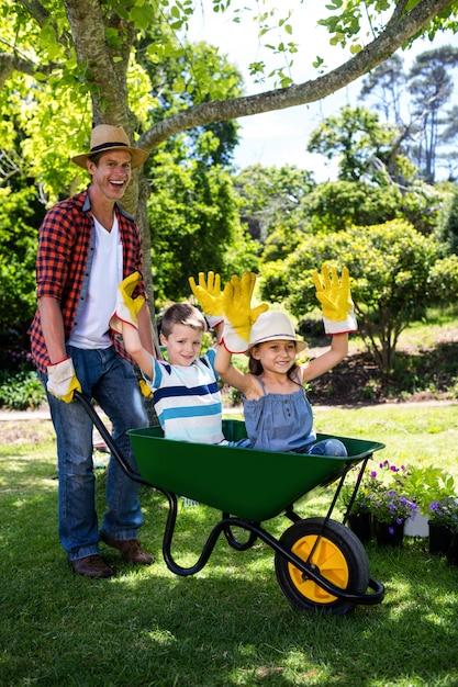 Pai carregando seu filho e filha em um carrinho de mão Foto Premium