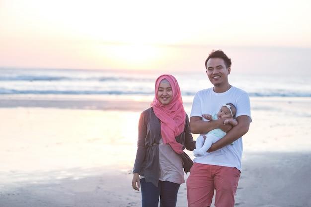 Pai com bebê recém-nascido na praia se divertindo juntos Foto Premium