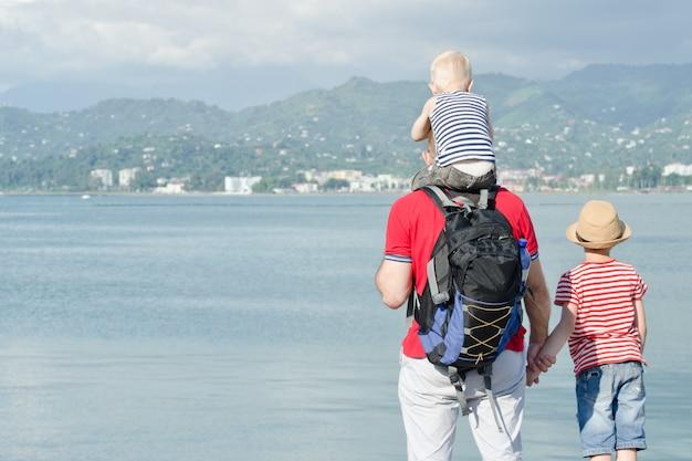 Pai com dois filhos ficar na praia. vista de trás Foto Premium