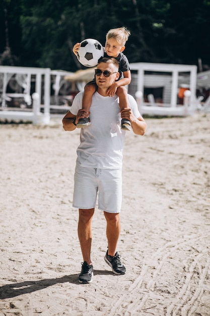 Pai com filho jogando futebol na praia Foto gratuita