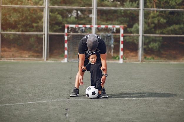 Pai com filho jogando futebol Foto gratuita