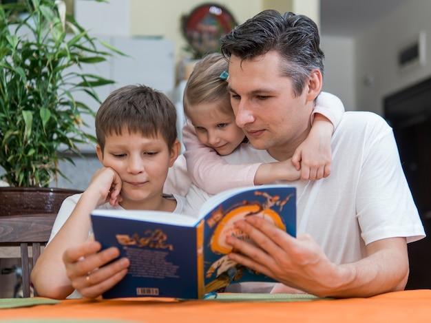 Pai com filhos de irmão e irmã lendo um livro Foto gratuita