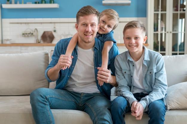 Pai com irmãos sentados no sofá Foto gratuita