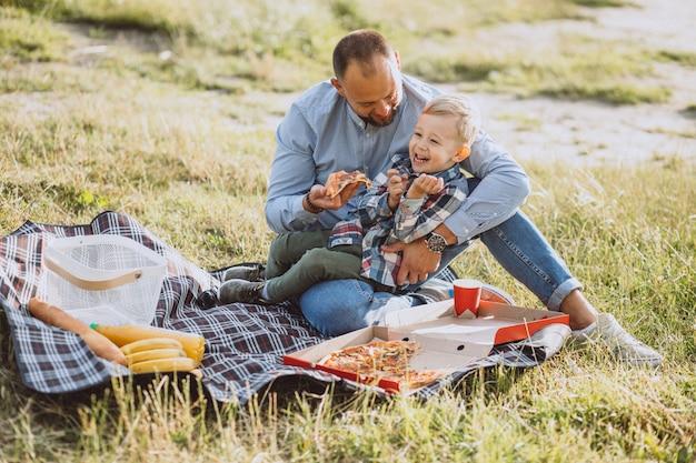 Pai com seu filho fazendo piquenique no parque Foto gratuita