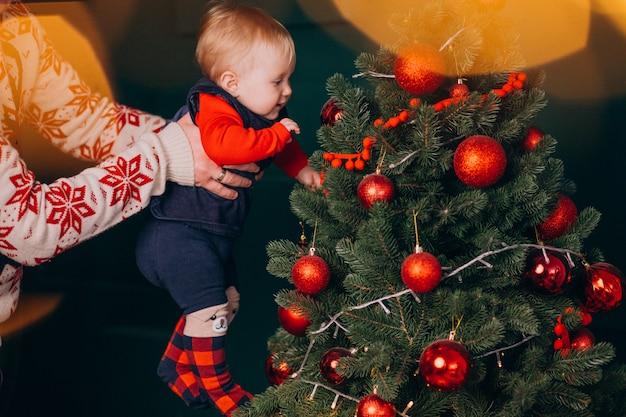 Pai com sua filha bebê pela árvore de natal Foto gratuita