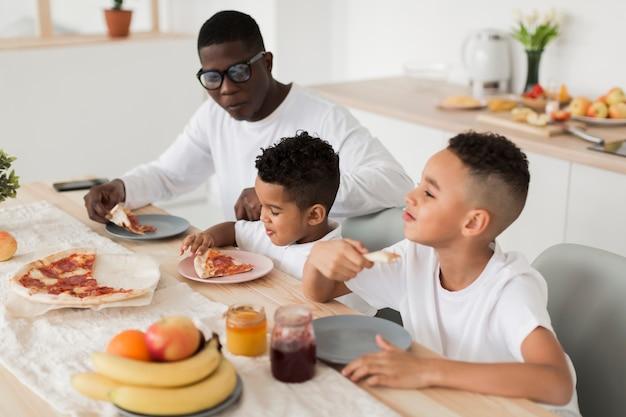 Pai comendo pizza com seus filhos juntos Foto gratuita
