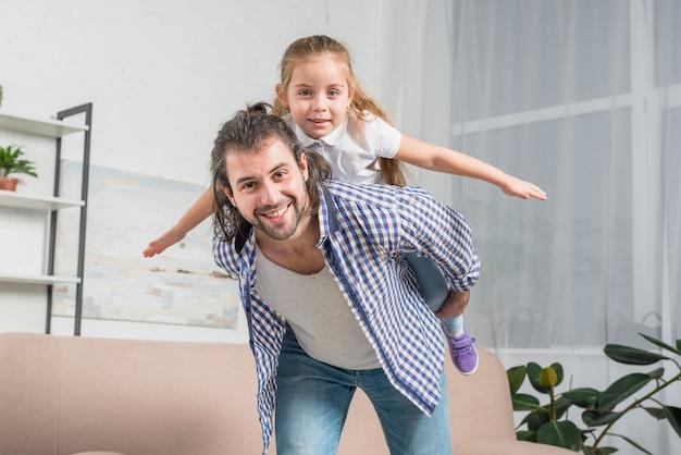 Pai dando um cavalinho de volta para sua filha Foto gratuita