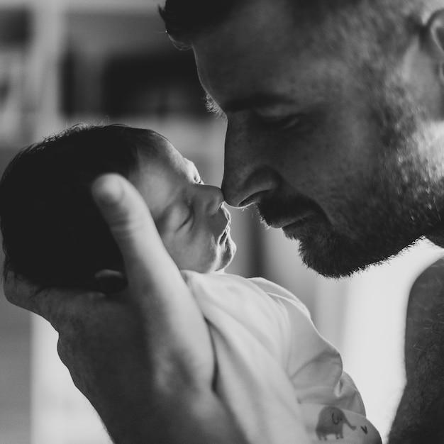Pai de close-up, tocando o bebê com o nariz Foto gratuita