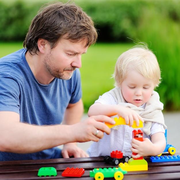 Pai de meia-idade com seu filho bebê brincando com blocos de plástico coloridos Foto Premium
