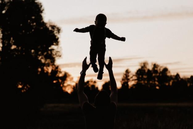 Pai de silhueta joga seu filho pequeno no campo ao pôr do sol Foto Premium