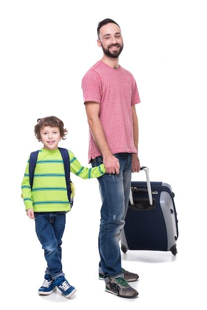 Pai de sorriso novo e seu filho com bagagem. Foto Premium