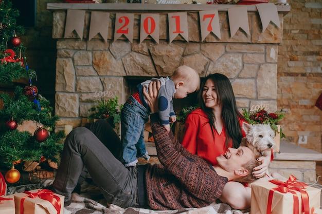 Pai deitado no chão com uma lareira em segundo plano enquanto levantando o bebê para cima e a mãe olha para eles sorrindo Foto gratuita