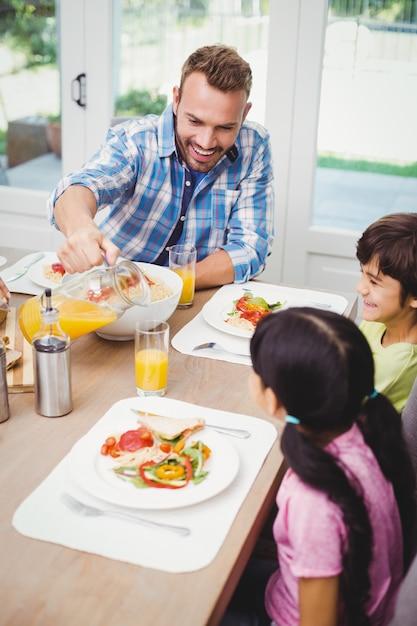 Pai derramar suco em copo com crianças Foto Premium