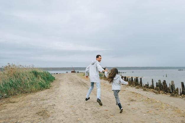 Pai e dauther vestida com capa de chuva correndo perto do lago e se divertir Foto Premium