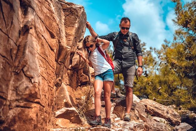 Pai e filha descendo de um penhasco Foto Premium