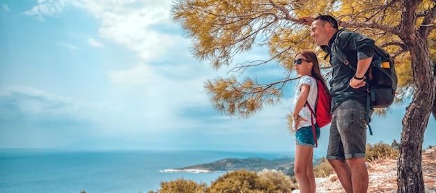 Pai e filha em pé em um penhasco à beira-mar Foto Premium