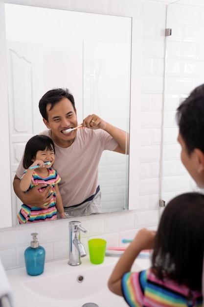 Pai e filha escovando os dentes juntos Foto Premium