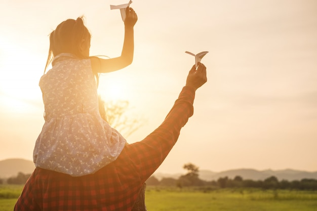 Pai e filha estão felizes com o avião de papel no prado. Foto Premium