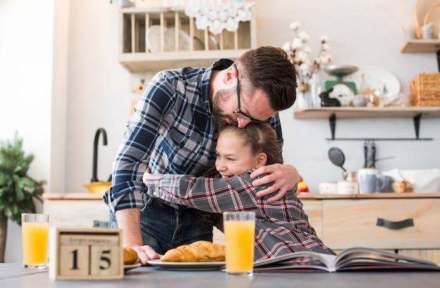 Pai e filha juntos na mesa de café da manhã Foto gratuita