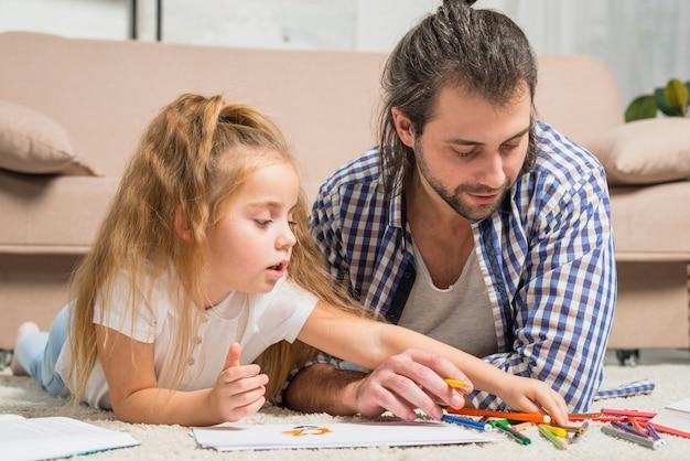 Pai e filha pintando no chão Foto gratuita