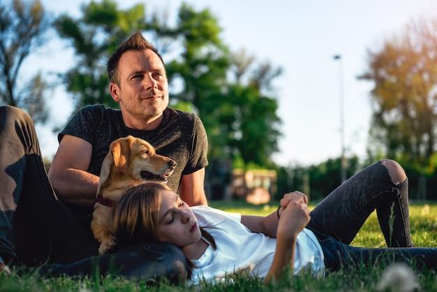Pai e filha relaxante no parque com cachorro Foto Premium