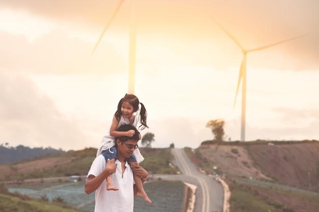 Pai e filha se divertindo para jogar juntos no campo de turbina de vento Foto Premium