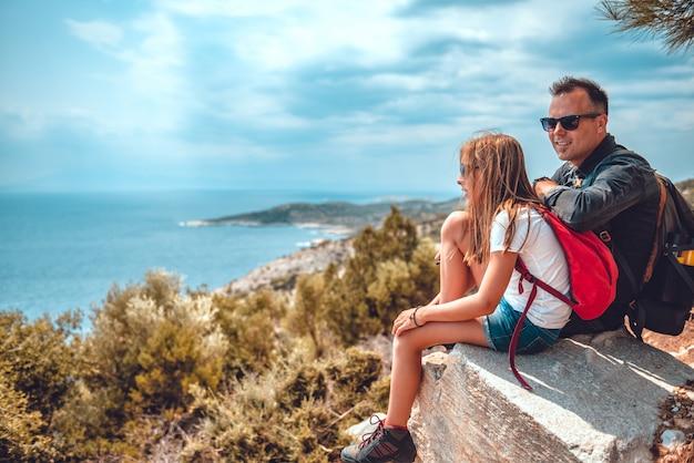 Pai e filha sentada na beira do penhasco à beira-mar Foto Premium