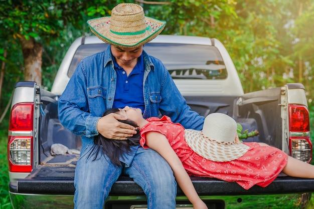 Pai e filha sentam-se na traseira de uma caminhonete Foto Premium