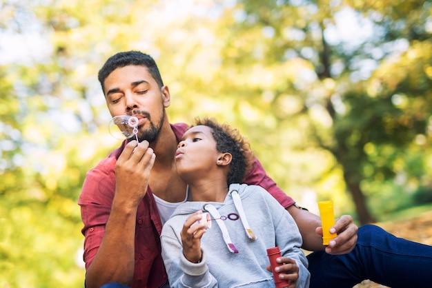 Pai e filha soprando bolhas de sabão se divertindo juntos Foto gratuita