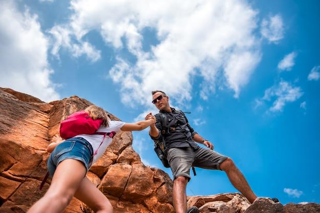 Pai e filha subindo no penhasco Foto Premium