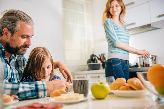 Pai e filha usando tablet na cozinha Foto Premium