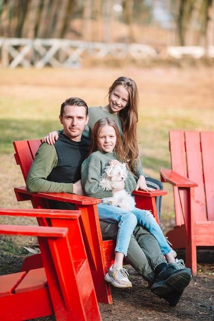 Pai e filhas fofos com cachorro ao ar livre Foto Premium