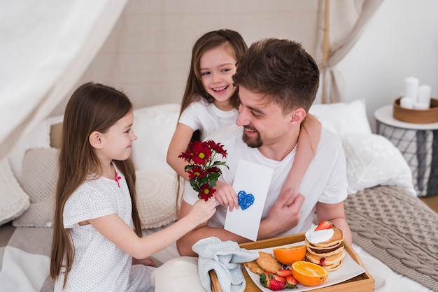 Pai e filhas tomando café da manhã no dia dos pais Foto gratuita