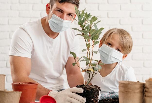 Pai e filho aprendendo sobre como plantar juntos em casa Foto gratuita