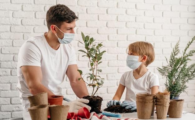 Pai e filho aprendendo sobre jardinagem em casa Foto gratuita