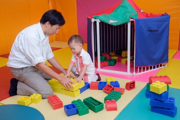 Pai e filho asiáticos se divertindo brincando com grandes blocos de plástico coloridos internos Foto Premium
