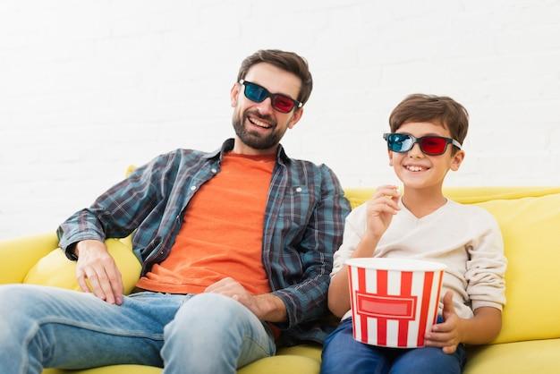 Pai e filho assistindo a um filme Foto gratuita