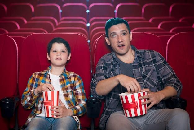 Pai e filho assistindo filme no cinema Foto gratuita