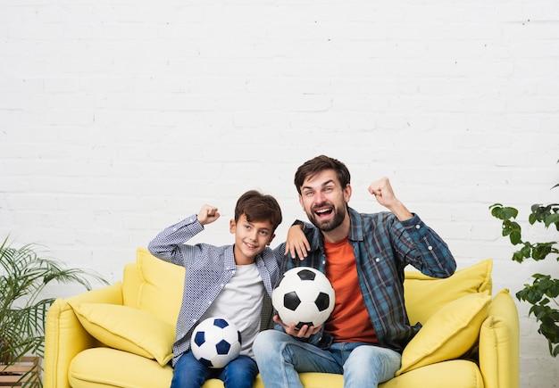 Pai e filho assistindo uma partida de futebol Foto gratuita