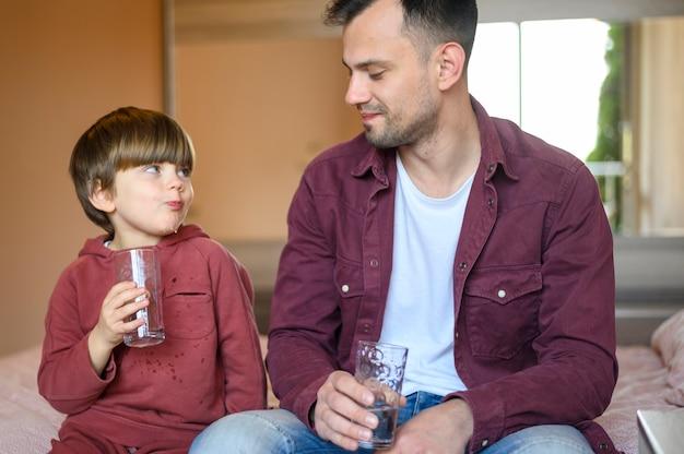 Pai e filho bebendo água Foto gratuita